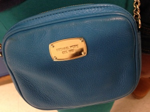 """A small,blue, crossbody, Michael Kors purse with a gold tag sewn on it with words """"Michael Kors"""" engraved."""