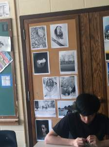 Wall of photos influences Kenwood student to work hard to get his work on the board which causes him to focus on his drawing.