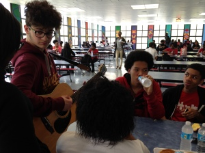 Kenwood Juniors eat and listen to a friend playing the guitar during 6th period lunch.