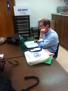 10. The Clincher: Mr. Ilhan Teacher at Kenwood Academy, the photo evokes an emotion that make one think. He is reviewing Projects that Seniors turned in as a final. He tired, out of it desperate, and mainly stressed out.
