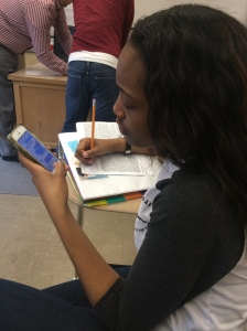 Sophomore Mariah Taylor is texting while doing her geometry work.  Her focus is straying due to her texting, which is hindering her from completing her assignment.