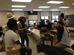 Kenwood Seniors gather around and talk in class after they turned in their Ap 2D Design Portfolios.