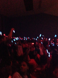 Kenwood Academy students gather in an assembly holding up red and blue glowsticks to demonstrate Bronco unity.
