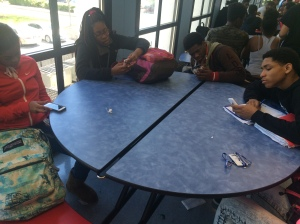 A group of Freshmen are sitting at a lunch table together not speaking to one another. They are so focused on their phones that they aren't able to socialize with each other.