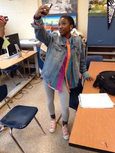 Senior Kayla Tucker poses for selfie with her cell phone. Tucker is in Art class while wearing a bright striped colored button up shirt, a denim jacket, grey leggings, and neon orange Converse.