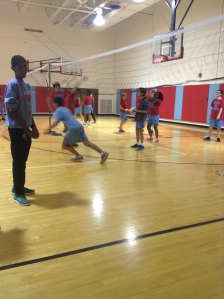 Kenwood students in 8th period gym are playing volleyball together as one student runs for the ball as the ball is leaving the area