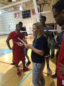 4.The Closeup Photo: Males Volleyball coach Ms.Howland talking to the team after practice. She was telling them what she expects to see in the next game if they wanted to advance in the playoffs.
