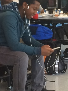 A Kenwood Student is enjoying the activity on his phone, which had all his attention.  He is sitting the opposite way of his peers at the table, which is facing outwards instead of in with everybody else.