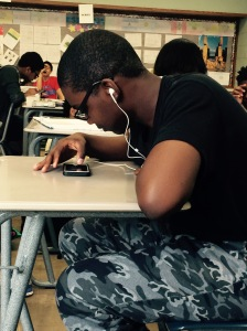 Freshman Julian Starks is using his phone to play a game while listening to music, during his AP Human Geography class.