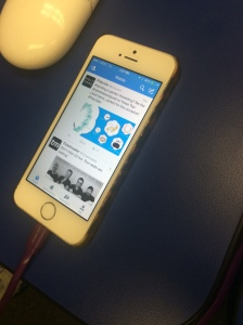 An Iphone 5 is charged while on twitter. Social media plays a big role in why teenagers pay more attention to their phones than their peers around them.