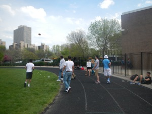 Kenwood students enjoy the spring climate by throwing a football back and forth on a clear day.