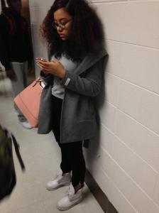 Freshman Taylor Wilson stands fashionably in the hallways of Kenwood texting. Wilson is wearing a dark grey peacoat, grey shirt, a pink purse, and white Timberland boots.