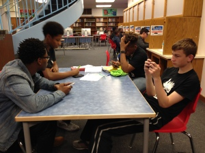 Kenwood students play games on their phones and talk about Latin homework in the library during their lunch period.