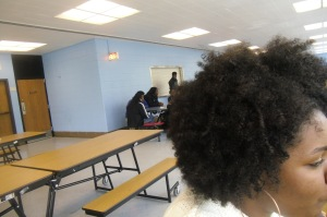 Kenwood freshman student sits in the lunch room with her curly and big natural afro.
