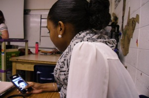 Sophomore student Anaya McDavid watchches Snapchat videos on her phone with her funky, curly, and classy ballerina bun.