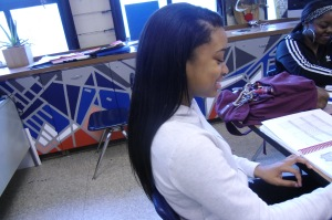 Junior student Kia Davis draws in art class while laughing with friends and showing off her black straight natural hair.