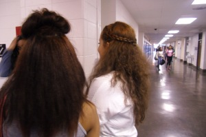 3 Kenwood students stand in the hallway and has a conversation while showing off their red funky curly and puffy hair.