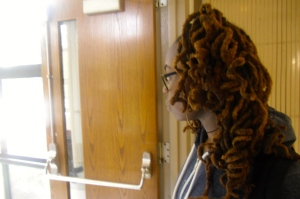 Sophomore student Asmina Turner stands in the halls of Kenwood showing off her curly dreadlocks.